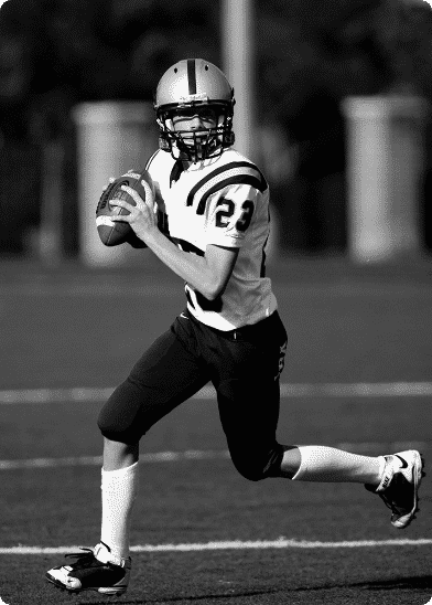 student quarterback running about to make a pass